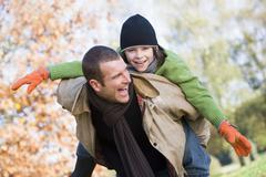 Father outdoors piggybacking son and smiling (selective focus) - stock photo