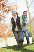 Senior couple outdoors running around and smiling (selective focus) - stock photo