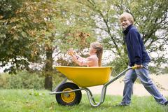 Young boy outdoors pushing young girl in wheelbarrow and smiling (selective Stock Photos