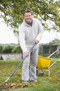 Man outdoors raking leaves near wheelbarrow and smiling (selective focus) Stock Photos