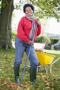 Woman outdoors raking leaves near wheelbarrow and smiling (selective focus) - stock photo