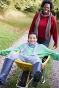 Mother outdoors pushing son in wheelbarrow and smiling (selective focus) Stock Photos