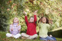 Three young children sitting outdoors throwing leaves in air and smiling - stock photo