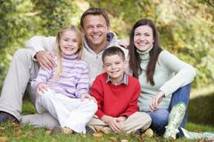 Family sitting outdoors smiling (selective focus) Stock Photos