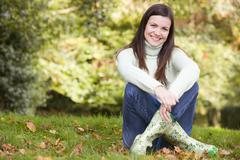 Woman sitting outdoors smiling (selective focus) - stock photo