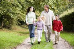 Family walking on path outdoors smiling (selective focus) - stock photo