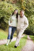 Couple walking outdoors on path in park smiling (selective focus) - stock photo
