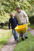 Father and son walking on path pushing wheelbarrow Stock Photos
