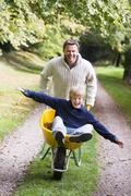 Man and young boy walking on path outdoors with wheelbarrow smiling (selective Stock Photos