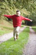 Young boy running on path outdoors smiling (selective focus) Stock Photos