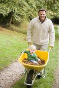 Man walking on path outdoors pushing baby in wheelbarrow and smiling (selective Stock Photos