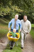 Two men walking on path outdoors pushing baby in wheelbarrow and smiling - stock photo