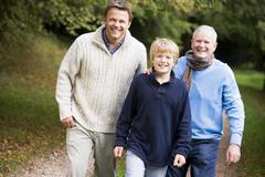 Two men and young boy walking on path outdoors smiling (selective focus) - stock photo