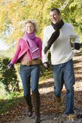 Couple running outdoors on path in park smiling (selective focus) - stock photo