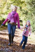 Woman and young girl walking on path outdoors smiling (selective focus) - stock photo