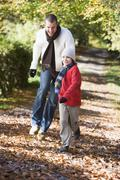 Man and young boy walking on path outdoors smiling (selective focus) Stock Photos