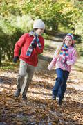 Two young children running on path outdoors smiling (selective focus) Stock Photos