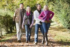 Two couples walking on path outdoors smiling (selective focus) - stock photo