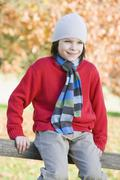 Stock Photo of Young boy outdoors sitting on fence smiling (selective focus)