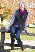 Woman outdoors sitting on fence smiling (selective focus) - stock photo