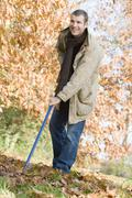 Man outdoors raking leaves and smiling (selective focus) - stock photo