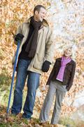 Couple outdoors raking leaves and smiling (selective focus) Stock Photos