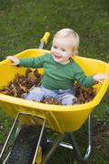 Baby outdoors sitting in wheelbarrow smiling (selective focus) - stock photo