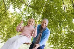 Grandfather outdoors pushing granddaughter on swing and smiling (selective - stock photo