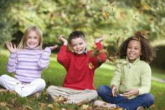 Three young children sitting outdoors in park throwing leaves in air and smiling - stock photo