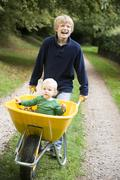 Young boy pushing baby brother in wheelbarrow Stock Photos