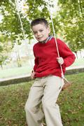 Young boy outdoors on tree swing smiling (selective focus) - stock photo