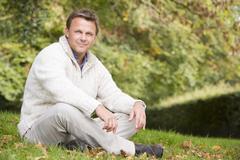 Man sitting outdoors smiling (selective focus) Stock Photos