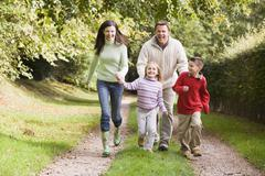 Family outdoors walking on path holding hands and smiling (selective focus) - stock photo