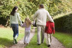 Family outdoors walking on path holding hands (selective focus) Stock Photos