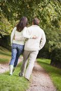 Couple walking outdoors on path in park (selective focus) - stock photo