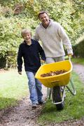 Father and son pushing wheelbarrow on path Stock Photos