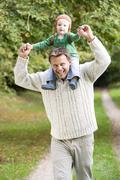 Father giving baby son piggyback Stock Photos