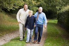 Two men and young boy walking on path outdoors smiling (selective focus) Stock Photos