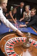 Group of people in casino playing roulette and smiling (selective focus) - stock photo