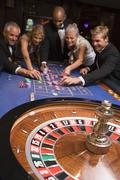 Group of people in casino playing roulette and smiling (selective focus) Stock Photos
