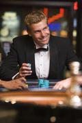 Man in casino playing roulette and smiling (selective focus) Stock Photos