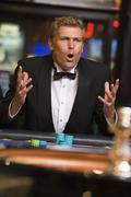 Man in casino playing roulette and losing (selective focus) - stock photo