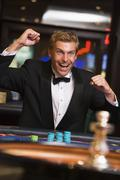 Man in casino winning at roulette and smiling (selective focus) Stock Photos