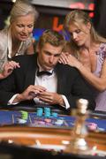 Three people in casino playing roulette smiling (selective focus) - stock photo