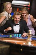 Three people in casino playing roulette smiling (selective focus) Stock Photos