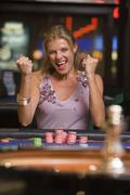Woman in casino winning roulette smiling (selective focus) - stock photo
