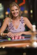 Woman in casino playing roulette smiling (selective focus) Stock Photos