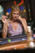Woman in casino playing roulette and holding chip (selective focus) - stock photo