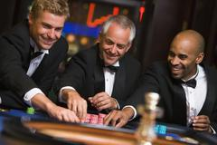 Three men in casino playing roulette smiling (selective focus) - stock photo