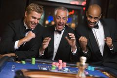 Three men in casino playing roulette smiling (selective focus) Stock Photos
